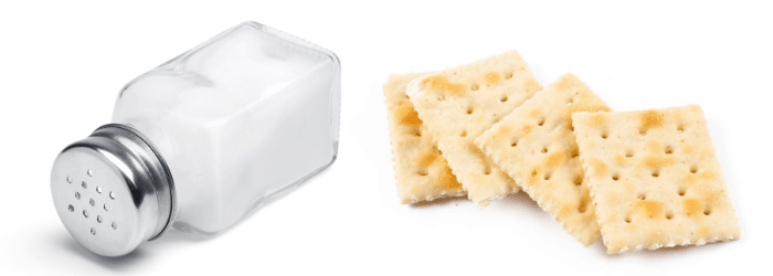 4 crackers and a bottle of salt on white background