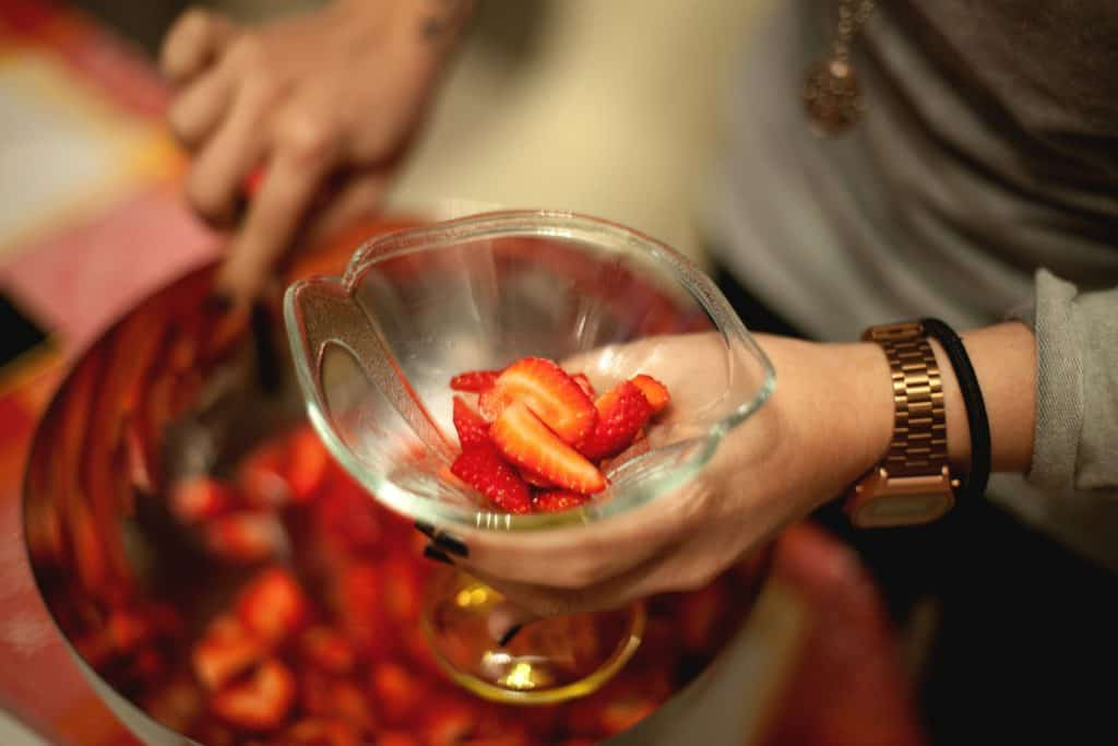 Person Holding a Glass With Slice Strawberries