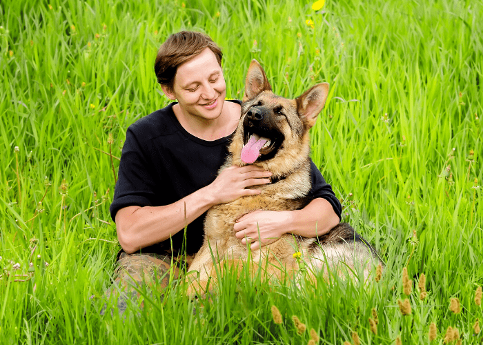 german shepherd and owner in the green grass