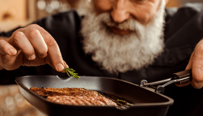man cooking steak in the frying pan